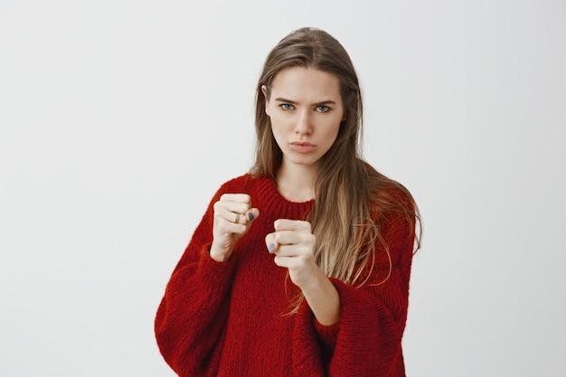 愛のために戦う準備ができている激しい深刻な女性。スタイリッシュな赤いルーズセーターで格好良いヨーロッパの女性モデル、上げられたくいしばられた握りこぶしでボクシングポーズで立って、顔をしかめ、防御する準備ができています