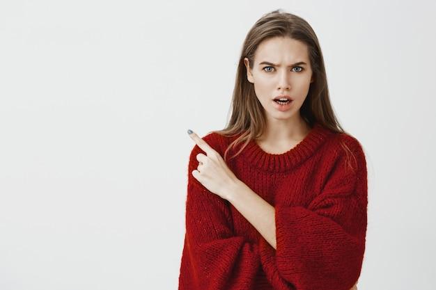 酔った男をパーティーに招待したのは誰ですか。赤いルーズセーターで不機嫌な怒っている若い女性の顔のスタジオ撮影、顔をしかめ、左上隅を指して友達と議論