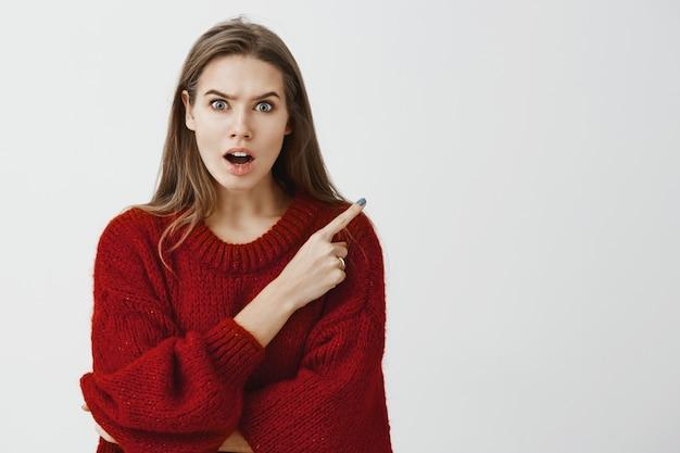 トレンディな赤いルーズセーターの衝撃的な強烈な魅力的なガールフレンド、後ろまたは右上隅を指して、うわさやゴシップを広めている間に驚かされ、オフィスでの最近の会議について話し合う