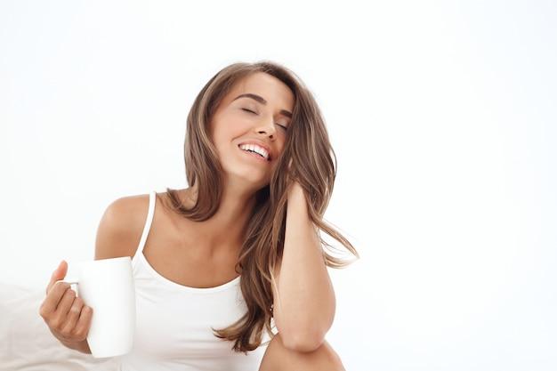 Молодая красивая женщина сидит на кровати, пьет чай, улыбается