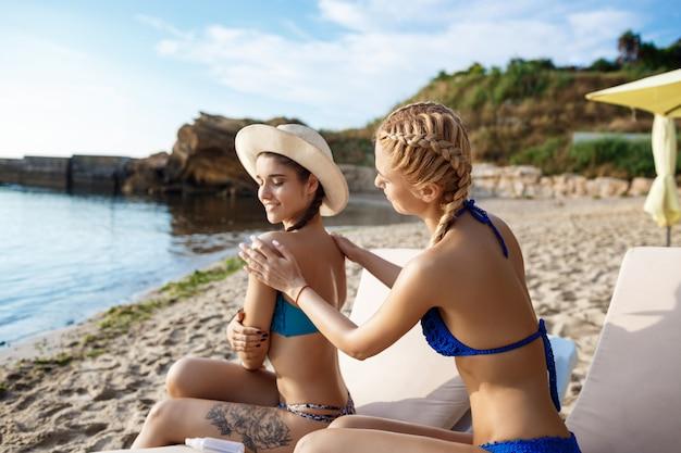 笑みを浮かべて、海辺で日焼け止めクリームを適用する水着で美しい女性
