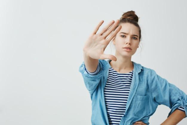 近づくことを禁じます。立ち止まっているか、十分なジェスチャーでカメラに向かって手を引いて自信を持って深刻な女性のスタジオ撮影