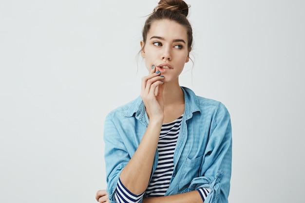Модная гламурная девушка с булочкой прическа смотрит в сторону, кусая губу и касаясь подбородка, концентрируясь на ком-то, мечтая или расставаясь, стоя.