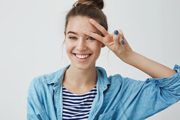 Студия талии расстреляла беззаботную стремящуюся восторженную привлекательную молодую европейскую женщину, улыбающуюся положительно белыми зубами, показывающую мир, счастливый знак прижатый рукой ко лбу, чувствуя себя счастливым приподнятым