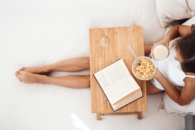 本とベッドの上に座って、上から朝食を食べて美しい女性。