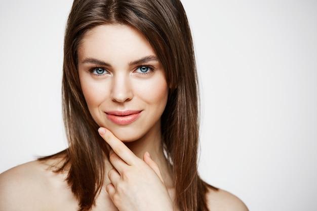 自然な裸の若い美しい女性が笑顔を占めています。美容とスパ。フェイシャルトリートメント。