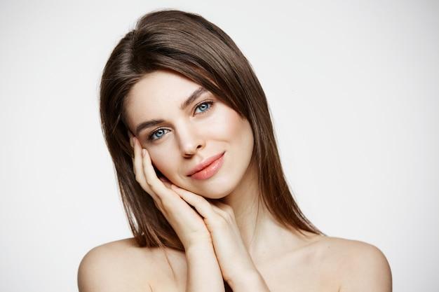 Голая молодая красивая женщина с естественным макияжем улыбается. косметология и спа. уход за лицом.