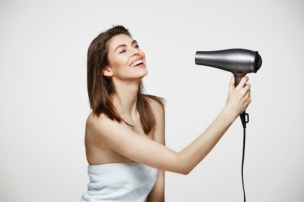 Жизнерадостная красивая женщина в полотенце, улыбаясь, смеясь петь с феном, делая смешное лицо салон красоты и косметологии.