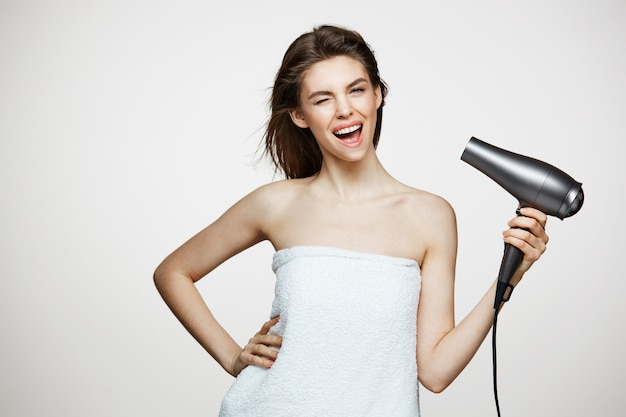 面白い顔を作るヘアードライヤーで歌って笑って笑ってタオルで陽気な美しい女性。美容スパと美容。
