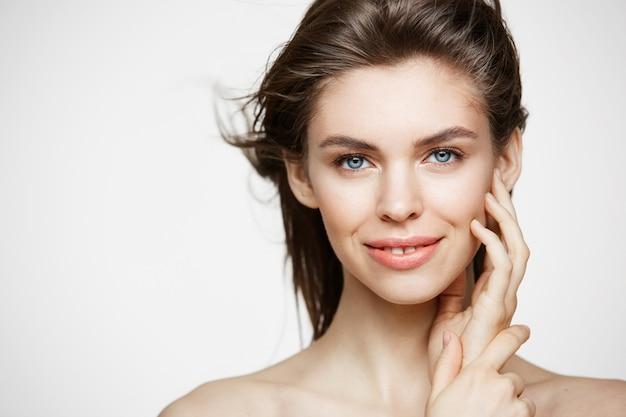 健康的な新鮮な肌と飛んでいる髪に触れる顔を笑顔で美しいブルネットの女性。