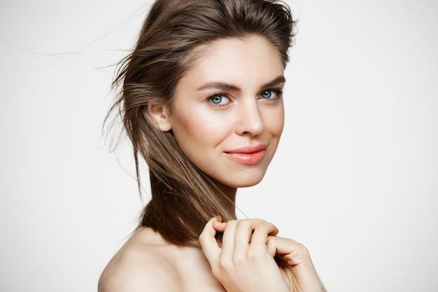 白い壁に触れる髪を笑って完璧なきれいな肌と美しい若い女性。フェイシャルトリートメント。