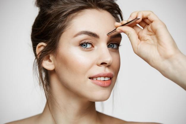 完璧なきれいな肌を持つ若い美しい女性は眉毛をピンセット。フェイシャルトリートメント。