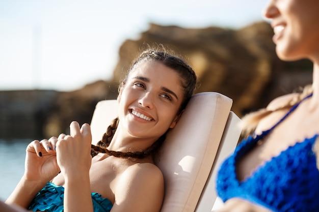 笑顔、日光浴、海の近くの長椅子で横になっている美しい女性