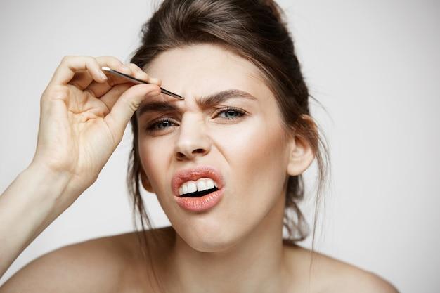 完璧なきれいな肌を持つ若いきれいな女性は、面白い顔を作る眉毛をピンセットにします。美しさとスパ。