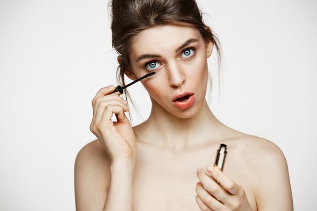 白い背景の上にカメラを見て開いた口で面白い美しい少女染料まつげ。美容健康と美容のコンセプトです。