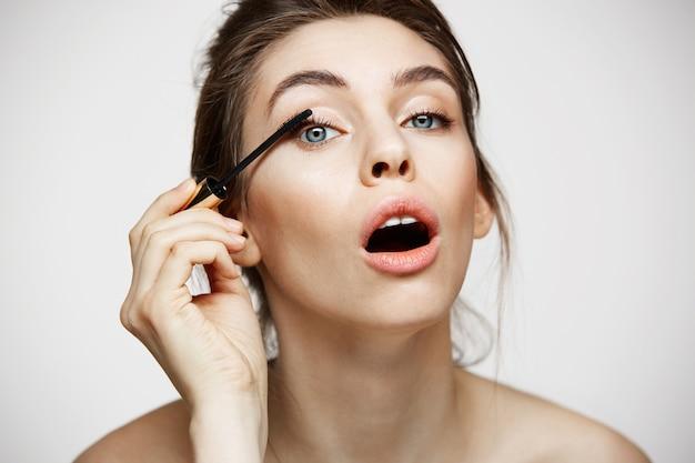 Смешные красивые ресницы краски девушки при раскрытый рот смотря камеру над белой предпосылкой. красота здоровье и косметология концепции.