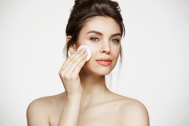 白い背景に笑みを浮かべて綿スポンジで顔を掃除して美しい自然なブルネットの少女。美容とスパ。
