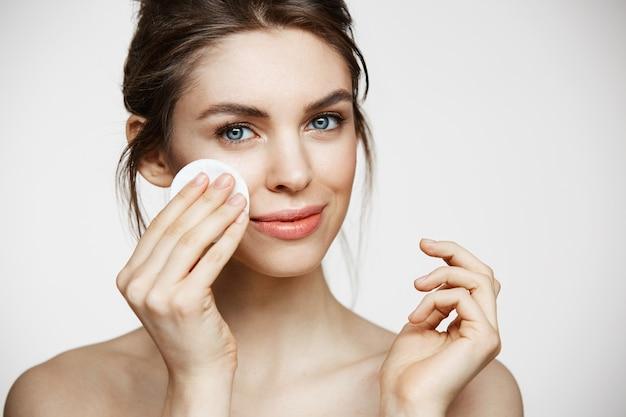 白い背景の上のカメラを見て笑みを浮かべて綿スポンジで顔を掃除かわいい美しい自然なブルネットの少女。美容とスパ。