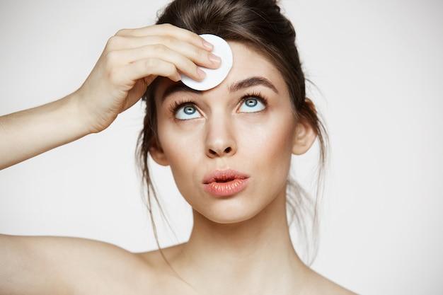 かわいい美しい自然なブルネットの少女は、白い背景に笑みを浮かべて綿スポンジで顔を掃除します。美容とスパ。