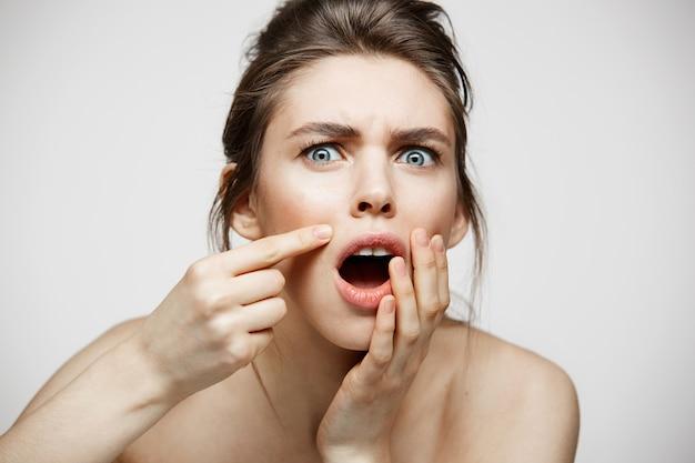 Молодая девушка брюнет раздражала ее кожи стороны угорь проблемы над белой предпосылкой. здоровье, косметология и уход за кожей.