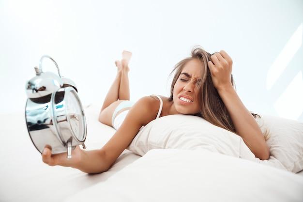 目覚まし時計を見て、ベッドに横になっている不機嫌な若い美しい女性