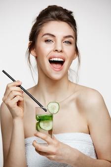白い背景の上にキュウリのスライスと水のガラスを保持しているカメラを見て笑って完璧なきれいな肌を持つ美しい少女。健康的な栄養。