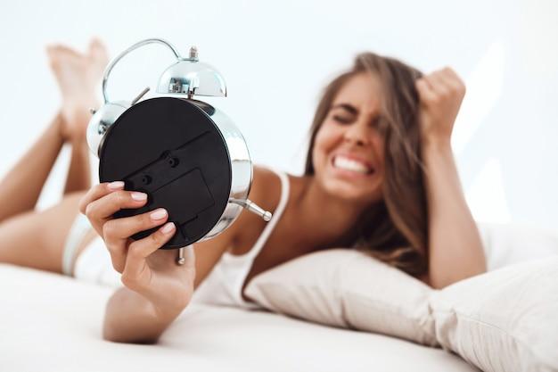 Недоволен молодая красивая женщина, лежа на кровати, глядя на будильник