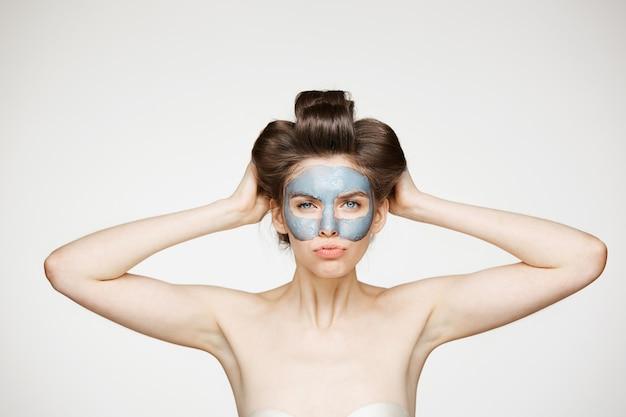 Молодая обнаженная женщина в бигуди и маска для лица хмурится. косметика по уходу за кожей и косметология.