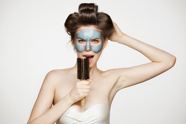 ヘアカーラーと櫛で歌うフェイシャルマスクの面白い若い女性の肖像画。美容とスキンケアのコンセプトです。