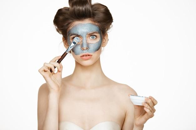 マックで顔を覆っているヘアカーラーの若い美しい女性。フェイシャルトリートメント。美容美容とスパ。