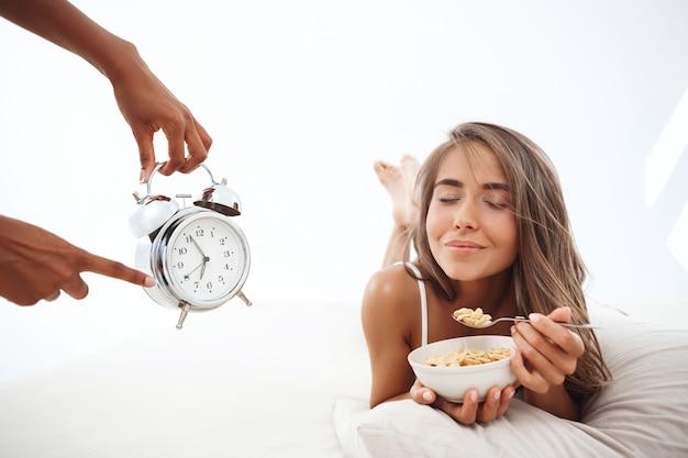 ベッドに横になっている美しい女性に目覚まし時計で時間を示す手