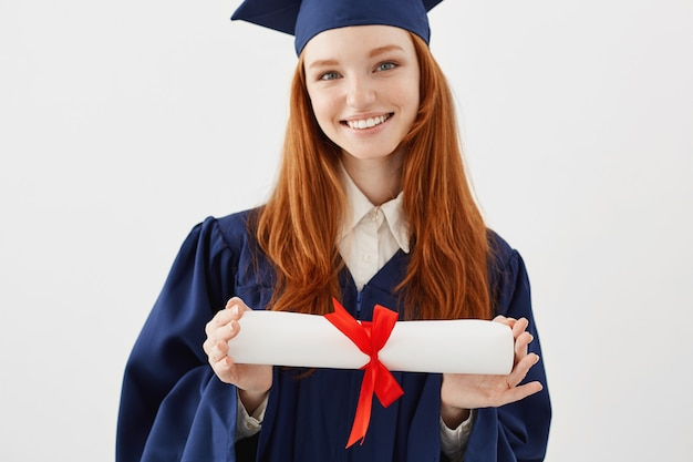 キャップを保持している卒業証書を笑顔で幸せなセクシーな女性卒業生の肖像画を閉じます。若い赤毛の女性学生将来の弁護士またはエンジニア。