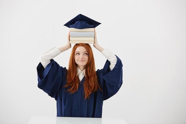 Выпускник имбирь женщина в мантии, улыбаясь, держа книги на голову под крышкой.