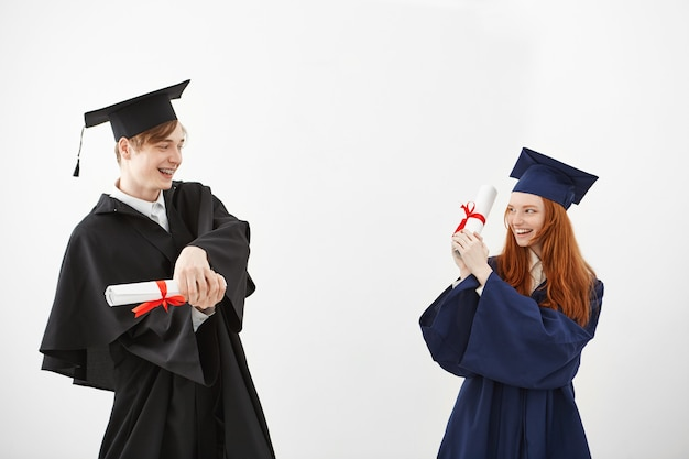 Веселые выпускники улыбаются, борются с дипломами.
