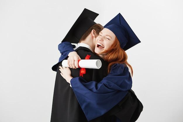 Два выпускника обнимаются. рыжая женщина смеется.