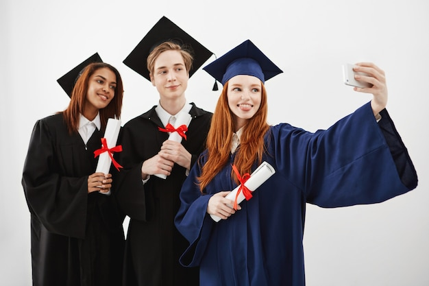 陽気な幸せな卒業生が自分撮りを作る笑顔をだまします。