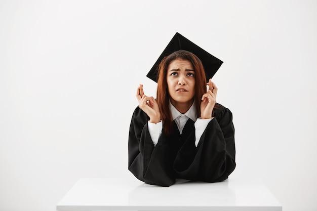 Слабонервная африканская студентка надеясь получить ее диплом, с пальцами пересекла белую стену сидя на таблице. концепция образования