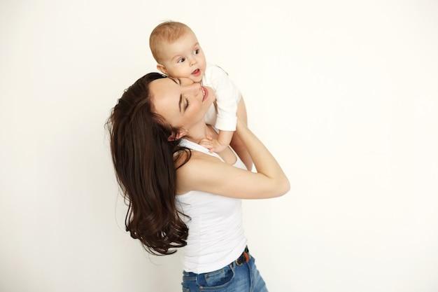 白い壁に彼女の赤ん坊の娘を保持している目を閉じて笑っている若い美しい幸せな母。