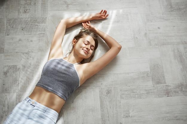 朝の日差しの中で床に横たわって笑って目を閉じて若い優しい美しい女性の肖像画。