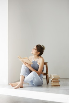 Молодая красивая нежная женщина, улыбаясь, глядя на окно, держа книгу, сидя на полу над белой стеной рано утром.