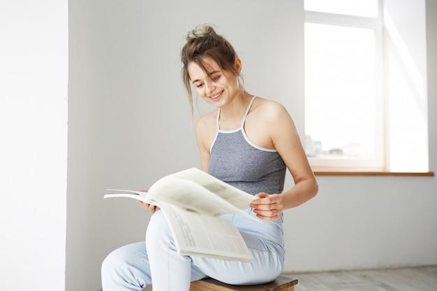 自宅の白い壁に椅子に座って本を読んで笑顔若い美しい幸せな女性の肖像画。