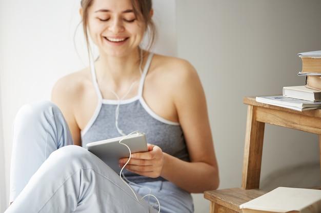 白い壁の上の床に座って音楽をストリーミングを聞いてタブレットを見て笑っているヘッドフォンの若い美しい女性。