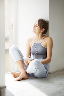 白い壁の上の床に座って音楽をストリーミングを聞いてタブレットを保持して楽しんでいるウィンドウを見て笑ってヘッドフォンで若い美しい女性。