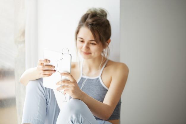 Портрет молодой подростковой жизнерадостной женщины в наушниках усмехаясь смотрящ интернет просматривать интернета таблетки занимаясь серфингом сидя около окна над белой стеной.