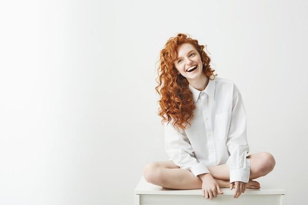 テーブルのポーズの上に座って笑っているシャツの優しい若い赤毛の女性。