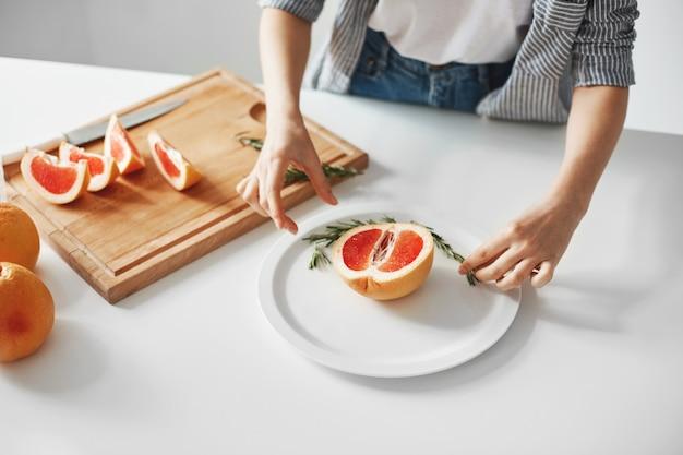 グレープフルーツとローズマリーの半分でプレートを飾る少女のクローズアップ。ダイエット健康食品。