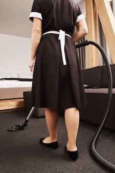 掃除機付きのクラシックなユニフォームクリーニングアパートのメイドの水平リアビュー。リビングルームで作業し、スペースをすっきりと整頓します。女性は雇用主の要求を満たすために最善を尽くします