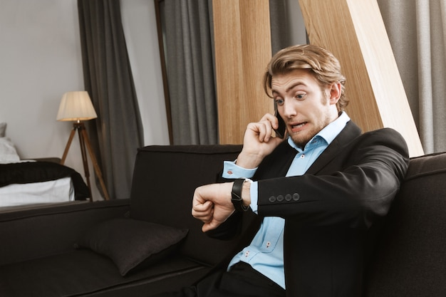 ブロンドの髪と黒いスーツを着たひげを持つ若者の肖像、怖がっている表情で会社の監督との会議に遅れている時計を見て