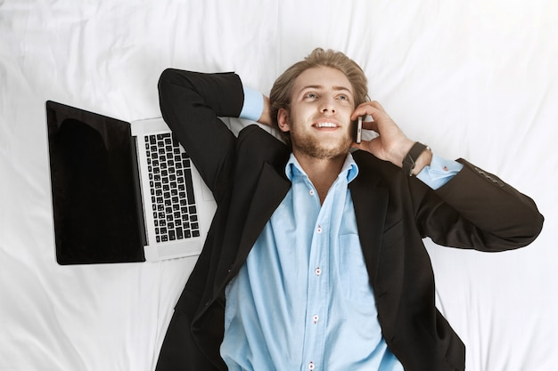 Закройте вверх по портрету радостного красивого бизнесмена лежа на кровати в костюме с компьтер-книжкой и сотовым телефоном. разговаривать с клиентом, радоваться его работе.