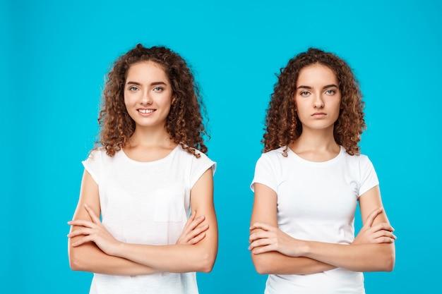 Две женщины близнецы позирует со скрещенными руками на синем.